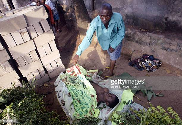 Martin Uzoma tries to cover the face of his relative Ikechukwu Okere, allegedly shot by anti-riots policemen on Ogbefere road, 06 December 2005 while...