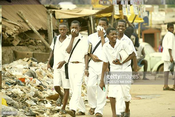 School children walk covering their nose from police tear gas shot to disperse members of the banned Movement for the Actualisation of the Sovereign...
