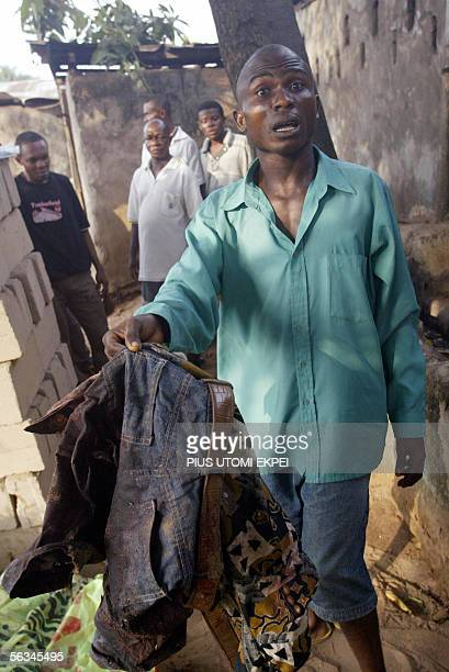 Twenty five-year-old Martin Uzoma holds the blood stained jeans and shirt worn by his relative Ikechukwu Okere as he was allegedly gunned down by...