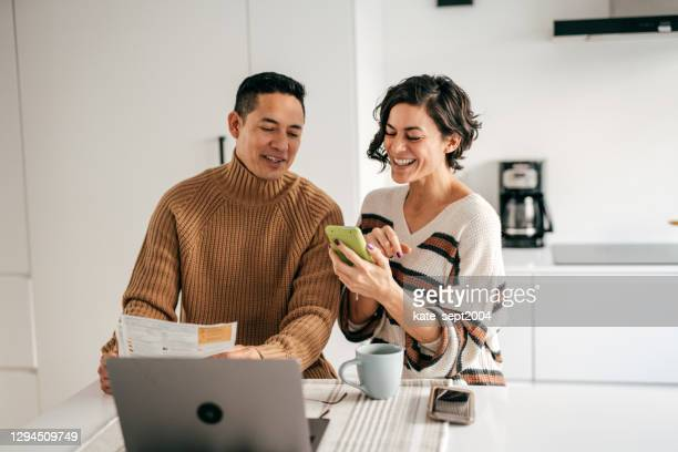 online banking for family budget - couple in the kitchen with bills - home ownership stock pictures, royalty-free photos & images