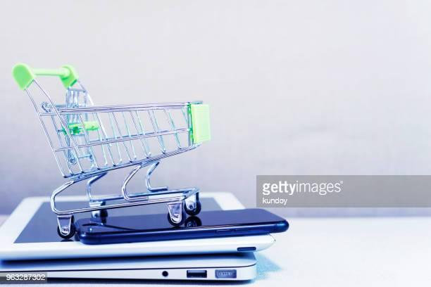 online business and e-commerce or shopping online concept. shopping basket on top of stack of laptop, tablet and mobile phone. wireless technology for business with free copy space. - goed gekleed stockfoto's en -beelden