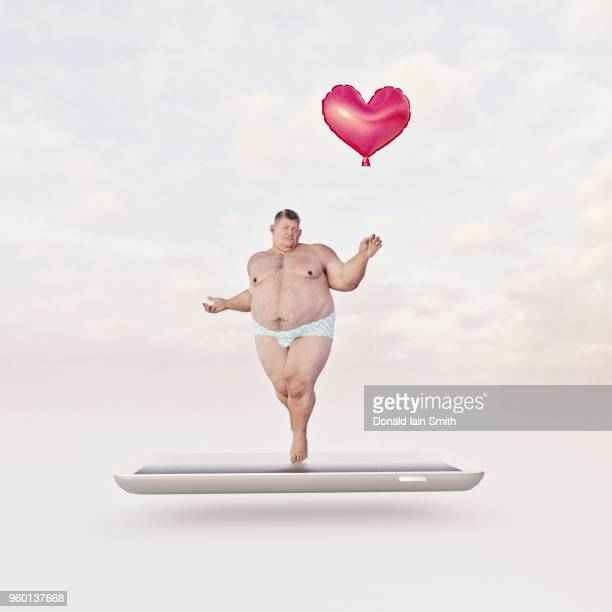 Online dating concept: overweight man in underwear holding red heart shape balloon standing on mobile phone