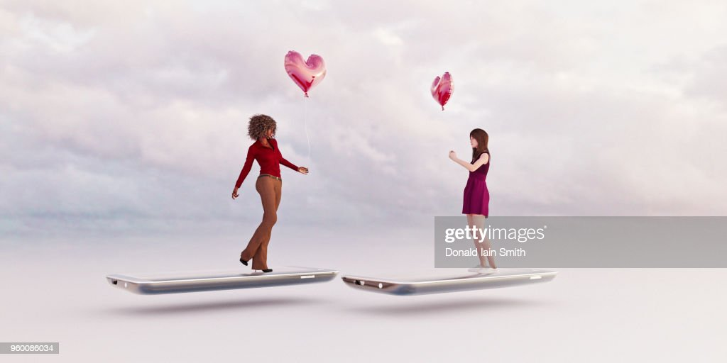 Online dating concept: same sex couple, two women, searching for a partner holding a heart shape red balloon standing on mobile phone : Stock-Foto