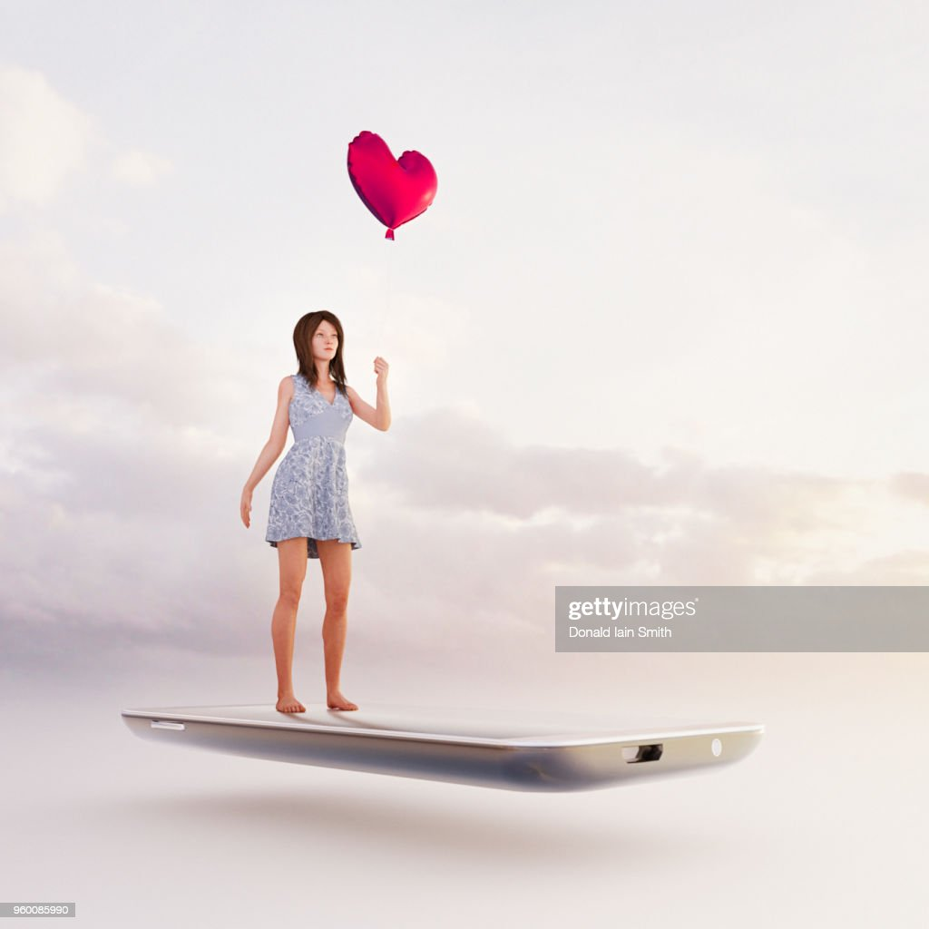 Online dating concept: searching for a partner holding a heart shape red balloon standing on mobile phone : Stock-Foto
