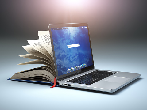Online library or E-learning concept. Open laptop and book compilation. 940972538