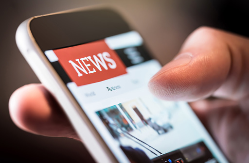Online news in mobile phone. Close up of smartphone screen. Man reading articles in application. Hand holding smart device. Mockup website. 1065782416