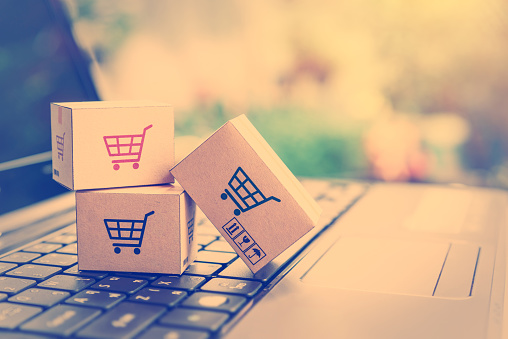 Online shopping / ecommerce and delivery service concept : Paper cartons with a shopping cart or trolley logo on a laptop keyboard, depicts customers order things from retailer sites via the internet. 1024926532
