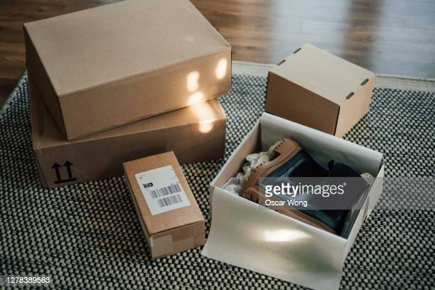 online shopping makes life easier - unboxing online purchase - clothing stock pictures, royalty-free photos & images