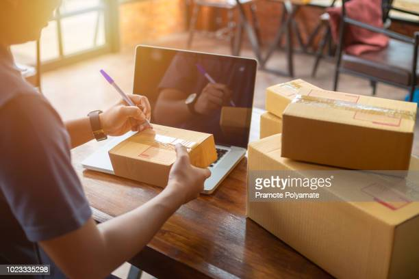 online shopping young start small business in a cardboard box at work. the seller prepares the delivery box for the customer, online sales, or ecommerce. - e commerce stock pictures, royalty-free photos & images