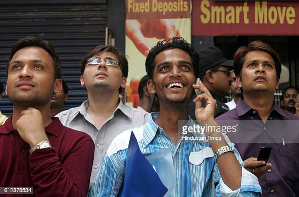 BSE Onlooker react as they watch the display at the Bombay Stock Exchange building in Mumbai