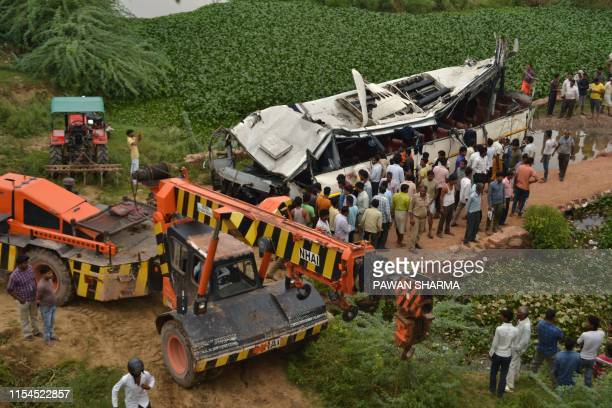 Onlookers and Indian police gather around the crumpled remains of a bus that crashed on the Delhi-Agra expressway, near Agra on July 8, 2019. - A bus...