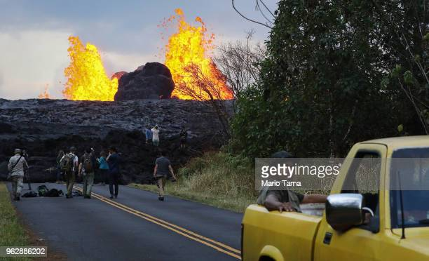 Onlookers and media gather as lava from a Kilauea volcano fissure erupts in Leilani Estates on Hawaii's Big Island on May 26 2018 in Pahoa Hawaii The...