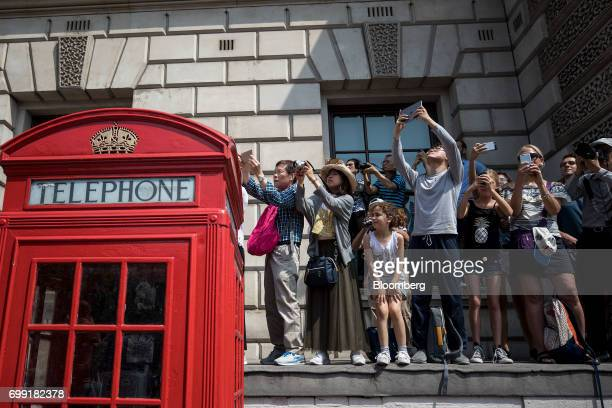 Onlookers and tourists stand on a wall near a traditional red telephone box to try and catch a glimpse of Queen Elizabeth II making her way to...