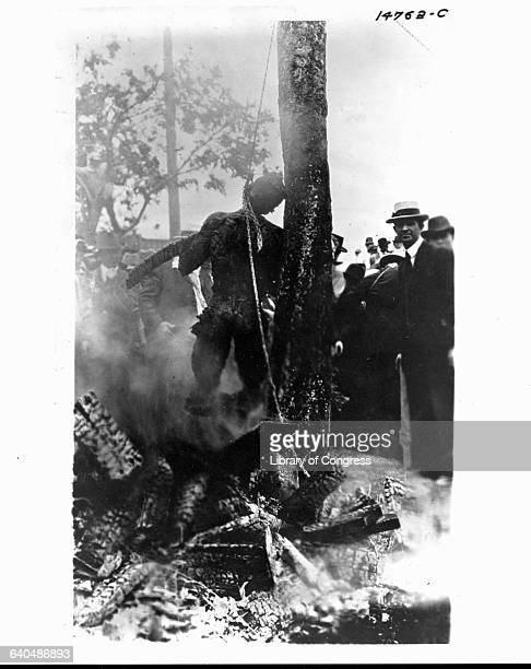 Onlookers crowd around the charred corpse of lynching victim Jesse Washington suspended from a noose leaning against the charred trunk of a tree Waco...