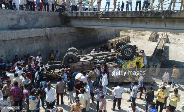 Onlookers gather around the debris of a truck that plunged off a bridge in Bhavnagar district about 200km from Ahmedabad in India's western Gujarat...
