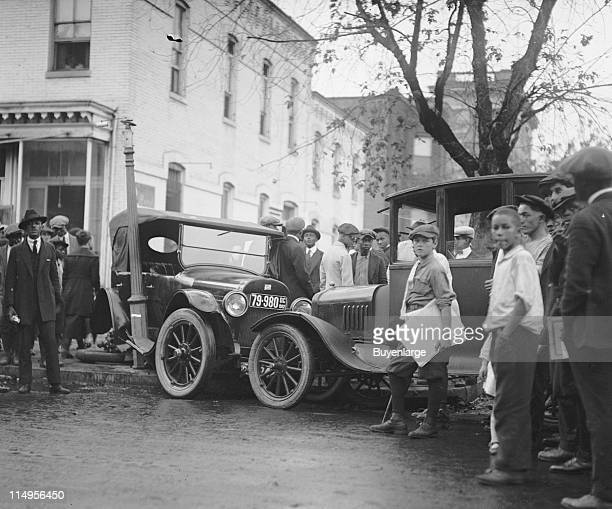 Onlookers gather around the scene of a car accident involving two automobiles early twentieth century The two cars hit head on with one automobile...
