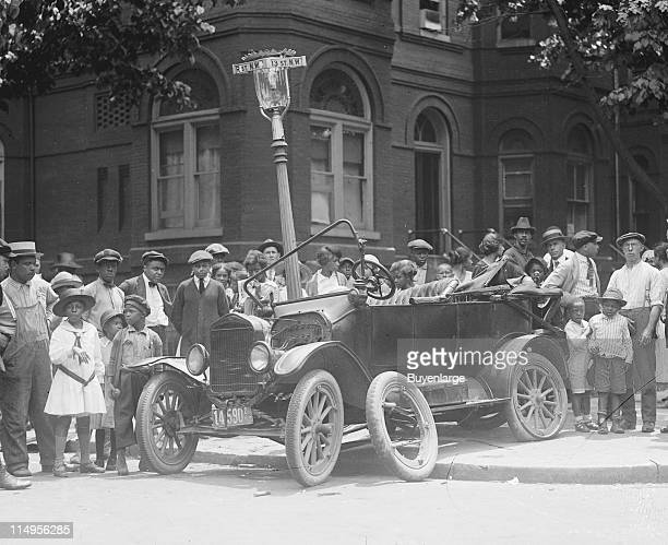 Onlookers gather at the corner of 13th and R streets at the scene of a car accident early twentieth century The car rests on the corner of the...