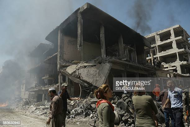 Onlookers gather at the site of a bomb attack in Syria's northeastern city of Qamishli on July 27, 2016. A double bomb attack killed at least 14...