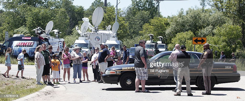 Onlookers gather at the site where FBI agents search a field for the alleged remains of former Teamsters' union president Jimmy Hoffa June 17, 2013 in Oakland Township, Michigan. The agents were acting on a tip provided by Tony Zerilli, 85, a former mobster, who was released from prison in 2008. Hoffa, who had reported ties to organized crime, went missing in July of 1975.