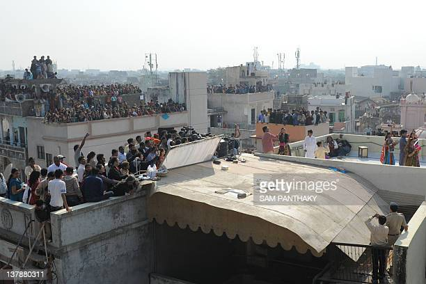 Onlookers gather on terraces to watch Indian Bollywood actor Amitabh Bachchan fly a kite at Kameshwar nipole the walled city area of Ahmedabad on...
