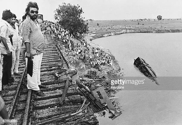 Onlookers gaze at the wreckage after a cyclone blew a crowded train off a bridge into the River Bagmati in Bihar killing hundreds of people June 1981