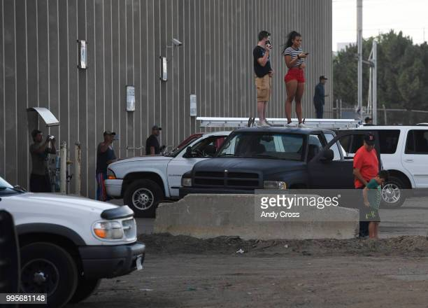 Onlookers get a higher angle on a fire in a large pile of crushed vehicles near 5600 York St July 10 2018