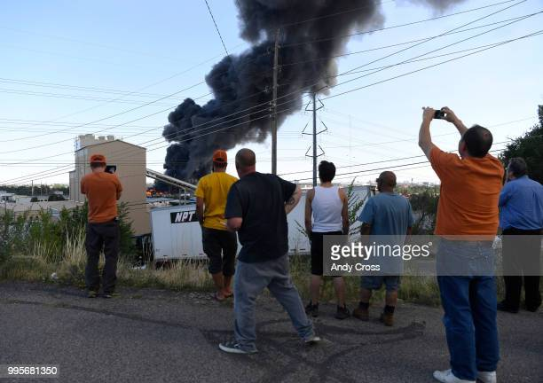 Onlookers get on angle on a fire in a large pile of crushed vehicles near 5600 York St July 10 2018