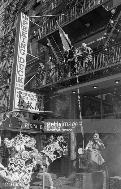 Onlookers hang a belt of lit firecrackers from a fire escape as dancers perform a traditional Lion Dance during the annual Chinese New Year...