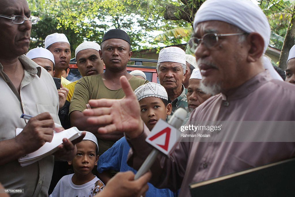 Onlookers listen as Abdul Hadi Awang, president of Malaysian Pan Islamic Party, reacts to a question during an interview in front of his home on April 26, 2013 in Rusila, Malaysia. Malaysia's 13th general election will be held on May 5.
