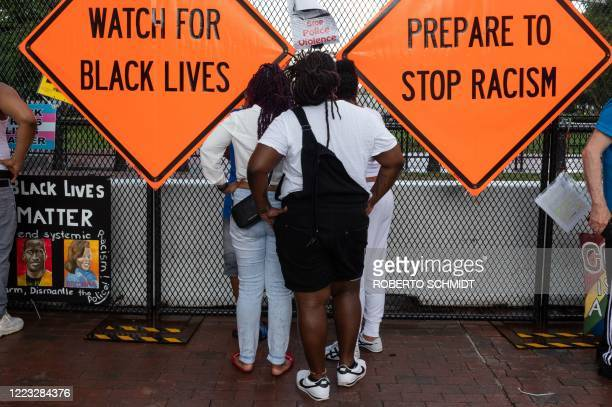Onlookers look at the White House near placards placed on a fence erected in front of Lafayette Park on June 27 in Washington, DC. - Wide spread...