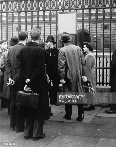 Onlookers outside Buckingham Palace read an official bulletin announcing the birth of Prince Charles to Queen Elizabeth II and Prince Philip London...