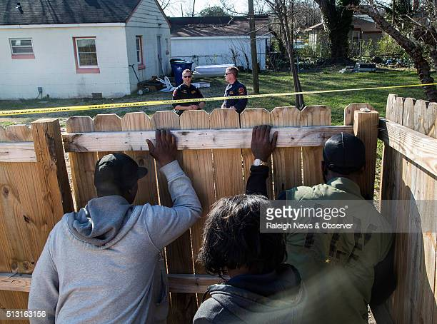 Onlookers peer through a fence as Raleigh police officers work the scene of a policeinvolved shooting near the intersection of Bragg and South East...
