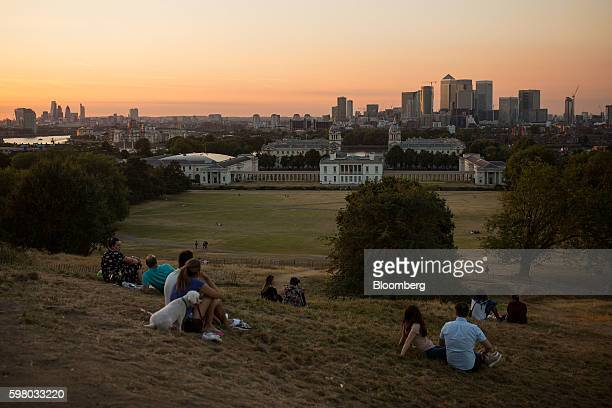 Onlookers sit in Greenwich Park to watch the evening sun set on the horizon beyond the Canary Wharf financial shopping and business district top and...