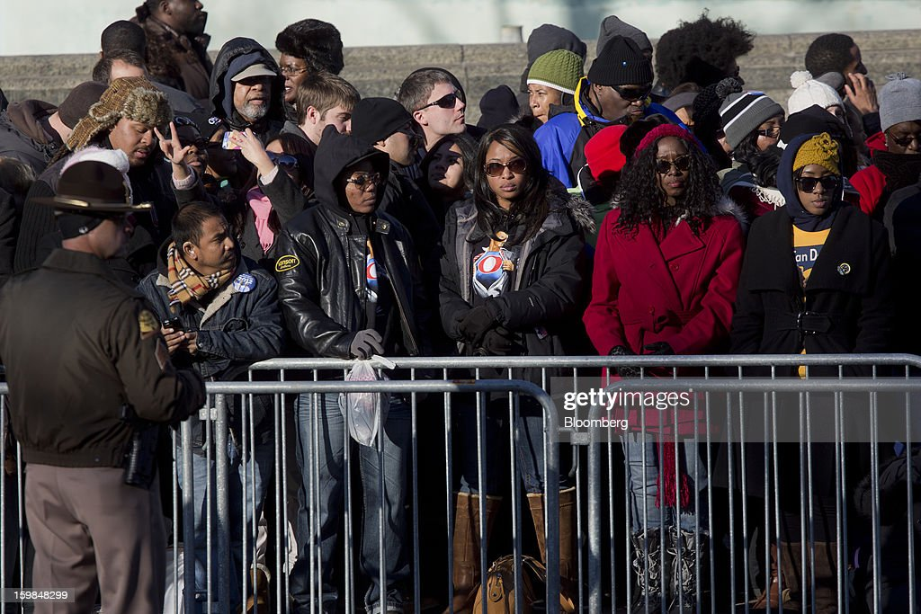 Onlookers stand along the parade route during the U.S. presidential inauguration in Washington, D.C., U.S., on Monday, Jan. 21, 2013. A crowd estimated by police to be as large as 700,000, including warmly dressed women with American flags stuck in their hair, a smattering of celebrities and many Republicans, gathered today to witness President Barack Obama take his second oath of office on the steps of the U.S. Capitol. Photographer: Victor J. Blue/Bloomberg via Getty Images