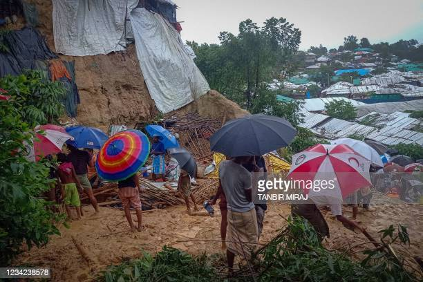 Onlookers stand as Rohingya refugees work amid the debris of houses in Balukhali camp on July 27, 2021 that were damaged after monsoon rains...