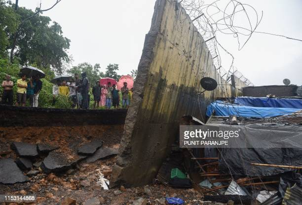 Onlookers stand behind a portion of the broken wall that collapsed in Mumbai on July 2 2019 At least 15 people were killed in India's financial...