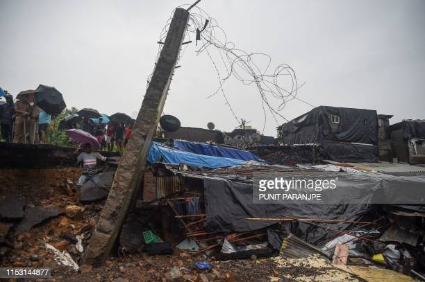 TOPSHOT Onlookers stand behind a portion of the broken wall that collapsed in Mumbai on July 2 2019 At least 15 people were killed in India's...