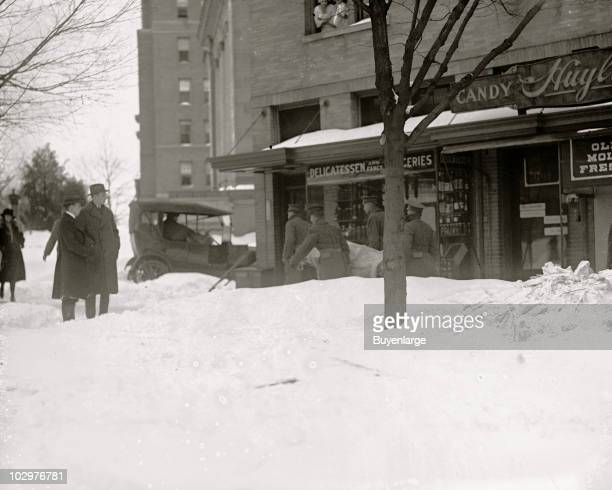 Onlookers stand by as rescue workers carry the dead from the wreckage of the Knickerbocker Theatre Washington DC January 29 1922 The structure's roof...