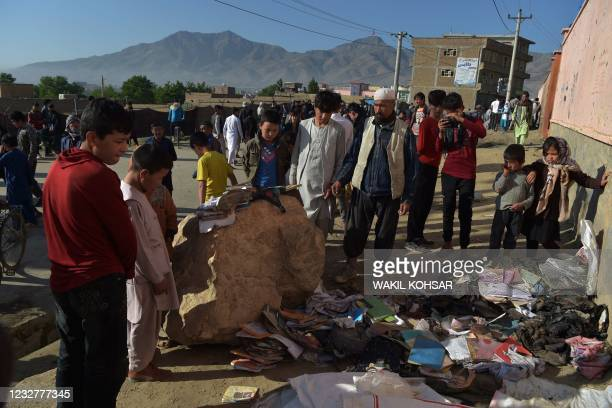 Onlookers stand next to a pile of backpacks and books of victims following yesterday's multiple blasts outside a girls' school in Dasht-e-Barchi on...