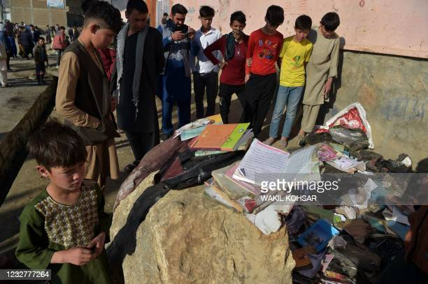 Onlookers stand next to the backpacks and books of victims following yesterday's multiple blasts outside a girls' school in Dasht-e-Barchi on the...