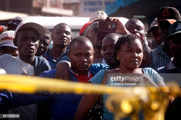 Onlookers survey the scene where two improvised explosive devices went off in Gikomba market on May 16 2014 in Nairobi Kenya Two improvised explosive...