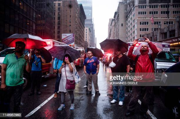 Onlookers take pictures on 7th Avenue after a helicopter crashlanded on top of a building in midtown Manhattan in New York on June 10 2019 Speaking...