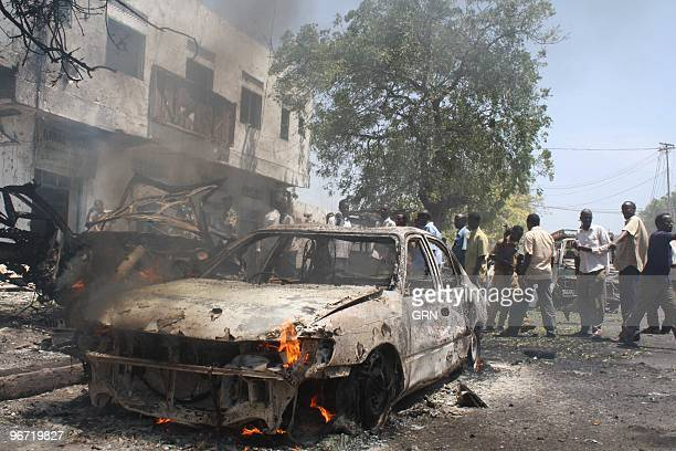 Onlookers view the wreckage of a suicide car bomb that targetted Somali government minister Sheikh Yusuf Siyad Indha Adde in a government controlled...