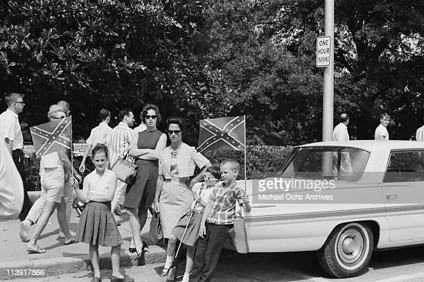 Onlookers watch a Ku Klux Klan rally in Atlanta Georgia USA 6 August 1965 Two children wave Confederate flags