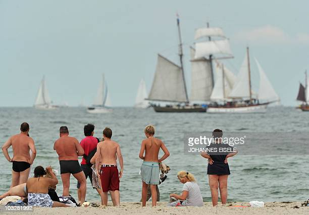 Onlookers watch a sailing boat making its way through the Baltic Sea during the Hanse Sail sailing festival in Warnemuende near Rostock northeastern...