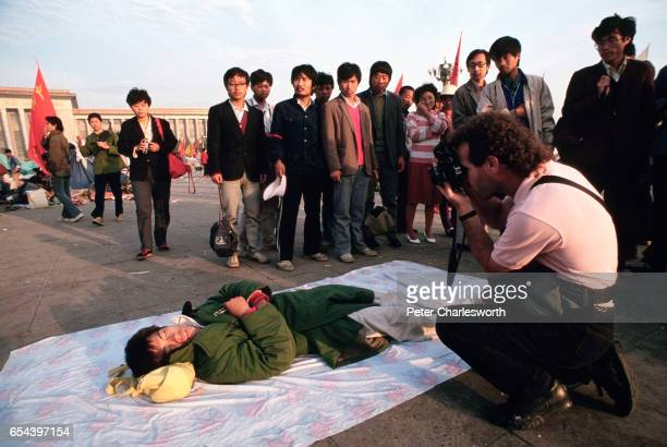 Onlookers watch American photographer Jeffery Aaronson takes picture of a prodemocracy demonstrator who is sleeping in Tiananmen Square Prodemocracy...