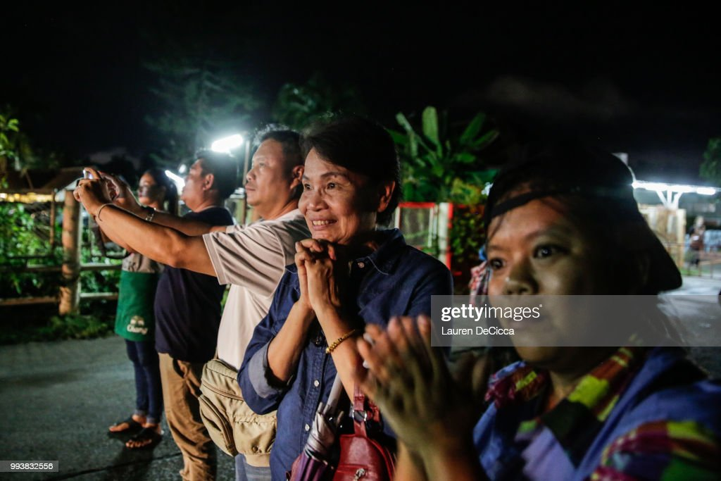 Onlookers watch and cheer as ambulances deliver boys rescued from a cave in northern Thailand to hospital in Chiang Rai after they were transported by helicopters on July 8, 2018 in Chiangrai, Thailand. Divers began an effort to pull the 12 boys and their soccer coach on Sunday morning after they were found alive in the cave at northern Thailand. Videos released by the Thai Navy SEAL shows the boys, aged 11 to 16, and their 25-year-old coach are in good health in Tham Luang Nang Non cave and the challenge now will be to extract the party safely.