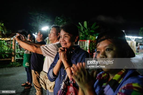 Onlookers watch and cheer as ambulances deliver boys rescued from a cave in northern Thailand to hospital in Chiang Rai after they were transported...