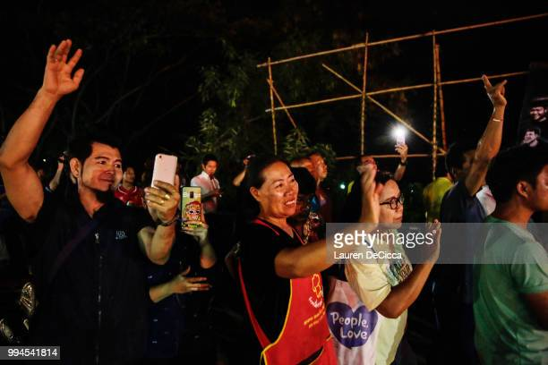 Onlookers watch and cheer as ambulances transport some of the rescued schoolboys from a helipad to a hospital on July 9 2018 in Chiang Rai Thailand...