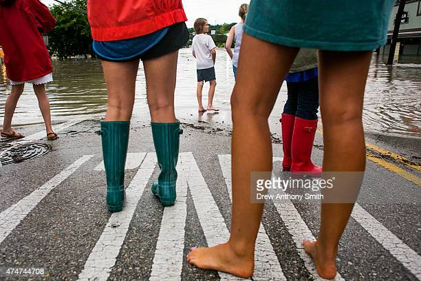 Onlookers watch as a street floods from days of heavy rain on May 25 2015 in Austin Texas Texas Gov Greg Abbott toured the damage zone where one...